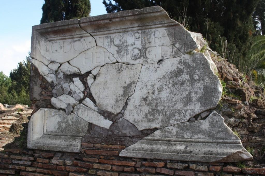 """Grafinscriptie van Fabius Hermogenes, Ostia 2015. Foto gemaakt door auteur. Zoals te zien op de afbeelding is de inscriptie op een aantal plaatsen niet compleet en ernstig beschadigd. De ontbrekende stukken tekst zijn door een """"archeologisch gelukje"""" echter zeer nauwkeurig te reconstrueren, omdat er een exacte kopie van de tekst is gevonden op het ruiterstandbeeld waar de inscriptie naar verwijst."""